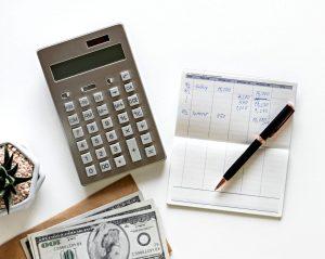 Miniräknare, konteringspapper, dollarsedlar och en penna.